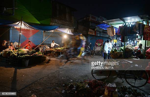 TOPSHOT Indian vegetable vendors wait for customers during a drop in custom following the decision to withdraw the current 500 and 1000 INR notes in...