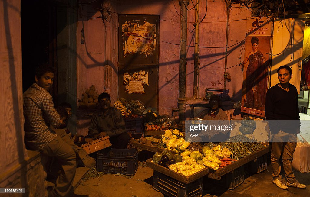 Indian vegetable vendors wait for customers under power lines in a corner of the Old Quarters in New Delhi on January 30, 2013. Emerging economies are set to grow faster than the developed economies over the next four decades and India is likely to become one of the three largest economies by 2050, said a Pricewaterhouse Coopers report. AFP PHOTO/ Andrew Caballero-Reynolds