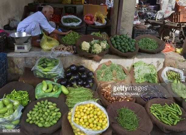 Indian vendor Amir Chand displays vegetables for sale at a roadside shop in Amritsar on June 5 2017 / AFP PHOTO / NARINDER NANU