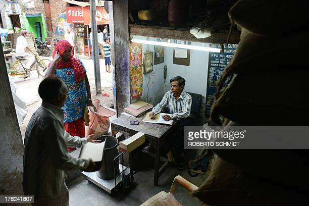 Indian vendor Brij Kishore tends to a customer at his Fair Price Shop a government food dispensary in the northern district of Jahangirpuri in New...