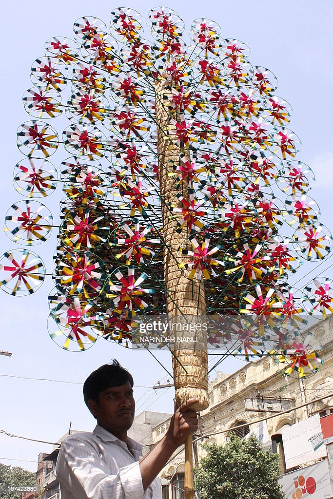 Indian vendor Krishan Mandal sells handmade paper fans as he waits for customers at the roadside in Amritsar on April 25, 2013.