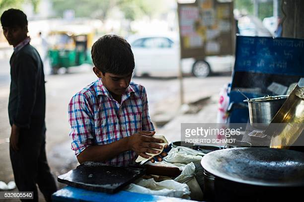 Indian vendor Navin prepares a popular Indian dish called paratha on a gas stove attached to his older brother's bicycle at a transport stand in a...