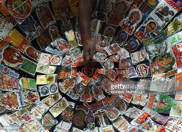 A Indian vendor selling stickers depicting various religions gods and godesses waits for customers at the corner of a crossroads in Mumbai on August...