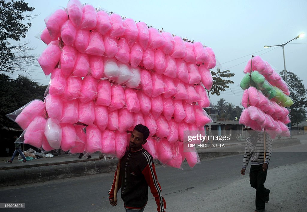 Indian vendors carry cotton candy in Siliguri on November 25, 2012. India's economy logged around 5.5 percent growth in the last financial quarter, the finance minister estimated on November 24, 2012-- a rate that could boost calls for lower interest rates to spur activityAFP PHOTO/ Diptendu DUTTA