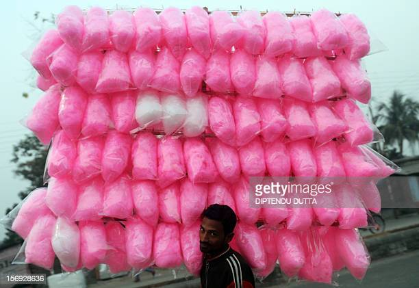 Indian vendors carry cotton candy in Siliguri on November 25 2012 India's economy logged around 55 percent growth in the last financial quarter the...