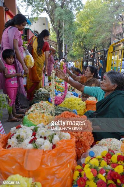 Indian vendors sell flower garlands to customers at a market in Bangalore on March 28 on the eve of Ugadi festival The Hindu New Year is celebrated...
