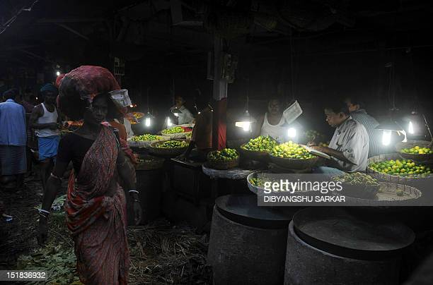 Indian vendors sell vegetables inside a wholesale market in Kolkata on September 12 2012 The Indian Meteorological Department has backtracked on...