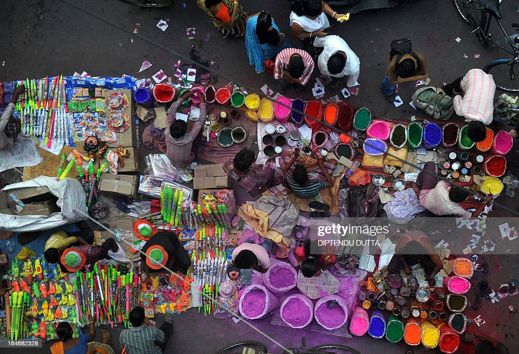 Indian vendors sells coloured powder known as 'Gulal' prior to the 'Holi' festival in Siliguri on March 26, 2013. Holi, also called the Festival of Colours, is a popular Hindu spring festival observed in India at the end of the winter season on the last full moon day of the lunar month and falls on March 27 this year. AFP PHOTO/Diptendu DUTTA
