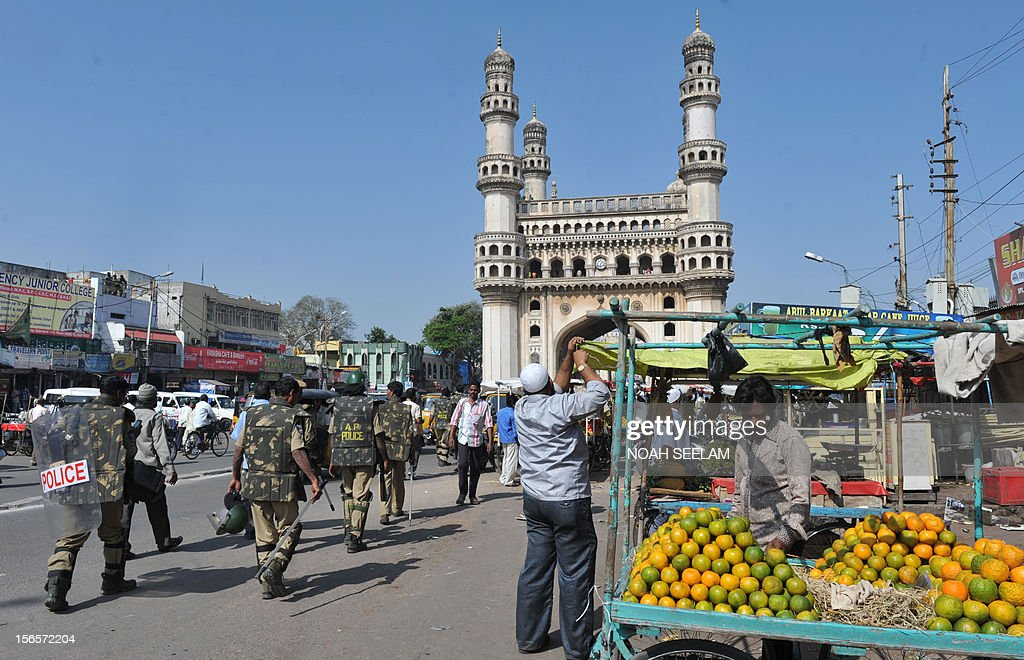 Indian vendors set up stalls as policemen patrol at the historic monument Charminar in the old city of Hyderabad on November 17, 2012. Restrictions were lifted on the movement of people and vehicular traffic around Charminar, where a mob indulged in stone pelting and trouble broke out after the noon prayers following the controversy over the newly erected structure near the Bhagyalaxmi temple. Muslims, supported by the Majlis-e-Ittehadul Muslimeen (MIM) party, opposed the move fearing that the temporary structure would pave the way for the permanent construction of a larger temple near the Charminar monument. AFP PHOTO / Noah SEELAM
