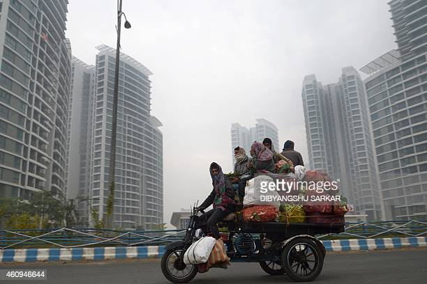 Indian vendors travel on a motorised tricycle as they transport vegetables in the shadow of high rise buildings on a foggy morning in Kolkata on...