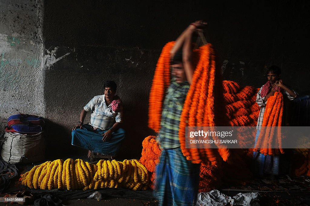 Indian vendors wait for customers at a wholesale flower market in Kolkata on October 18, 2012. Demand for flowers are high for the forthcoming Hindu festival Durga Puja, with added price increases this season due to rising diesel costs in the distribution chain. The five-day period of worship of Hindu goddess Durga, who is attributed as the destroyer of evil, commences on October 20. AFP PHOTO/Dibyangshu SARKAR