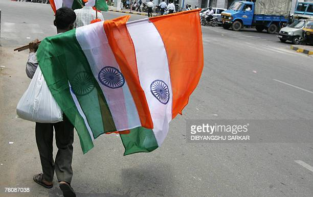 Indian vendors with Indian national flags cross the road to sell the flags to motorists and commuters on a busy city street in Bangalore 14 August...