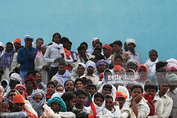 Indian village residents listen as unseen Chief Minister of the western Indian state of Gujarat and main opposition Bharatiya Janata Party prime...