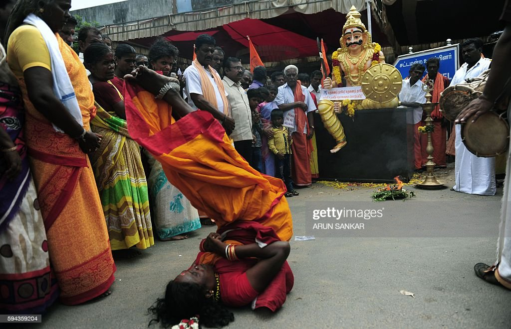A Indian village temple priest dressed as the Hindu god Shiva dances in while in a trance during a protest demanding an incread in benefits including...