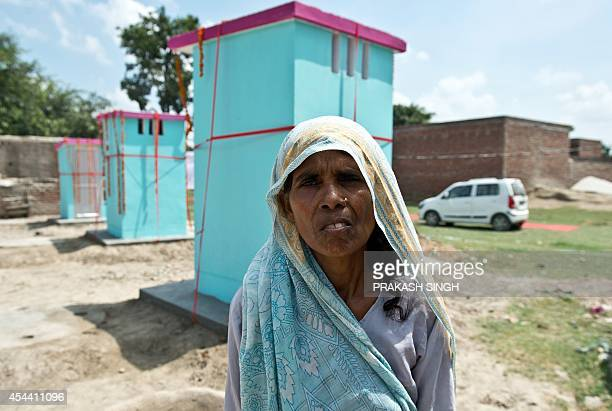 Indian villager Dhanwati Devi poses in front of newlybuilt toilets by NGO Sulabh International at Katra Sahadatgunj village in Badaun on August 31...