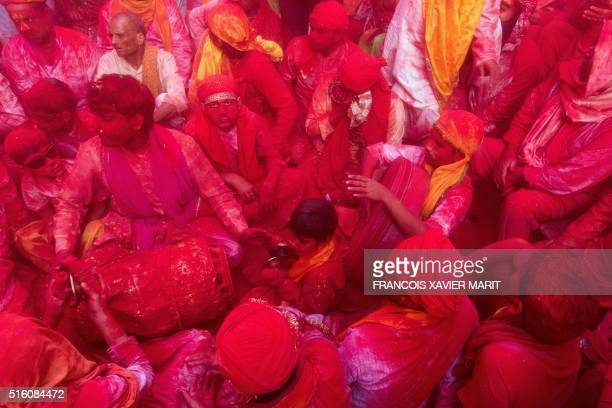 Indian villagers are covered with coloured powder during the Lathmar Holi festival at the Radha Rani temple in Barsana some 130kms from New Delhi on...