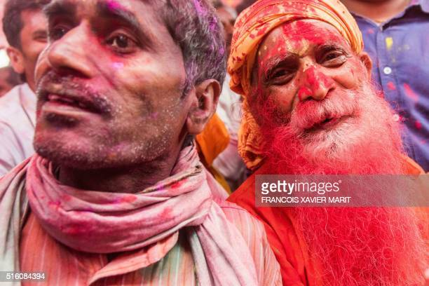 Indian villagers are covered with coloured powders during the Lathmar Holi festival at the Radha Rani temple in Barsana some 130kms from New Delhi on...