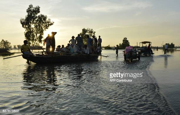 Indian villagers are seen on a boat next to other vehicles along a flooded state highway at Chachol village in Malda district in the Indian state of...