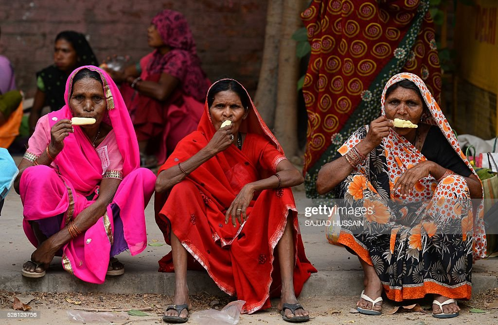 Indian villagers eat ice-cream as they sit on a roadside in New Delhi on May 4, 2016. / AFP / SAJJAD