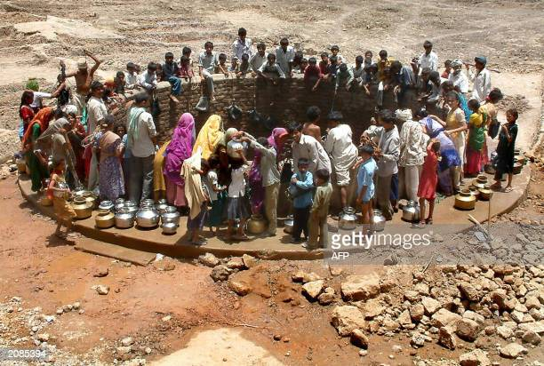 Indian villagers gather around a well to fill their pots with water at Natwargadh village 06 June 2003 some 110 kms from Ahmedabad the capital city...