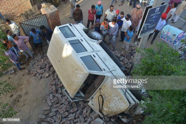Indian villagers gather by the wreckage of a vehicle after it rammed into an ice cream cart in an accident that killed six people including four...