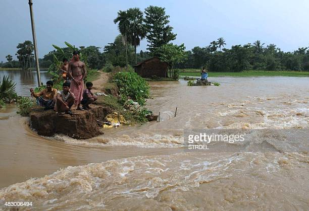 Indian villagers gather on land breached by floodwaters at Sibanipur in Udaynaranpur District some 60kms from Kolkata on August 5 as the eastern...