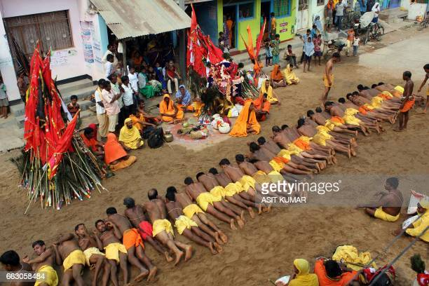 Indian villagers lay down in hot sand as part of a ritual during the annual Danda Nata festival at Galary village in Ganjam district of South Odisha...
