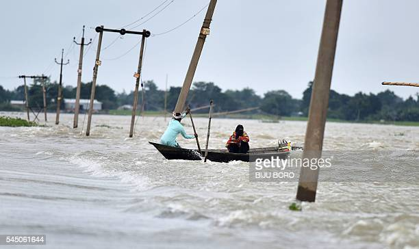 TOPSHOT Indian villagers paddle a boat along a submerged road in the floodaffected Ashighar village in the northeastern state of Assam on July 5 2016...