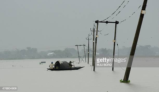 Indian villagers paddle their country boat in between electricity poles along a submerged road at the flood affected Pokoriya village some 75 kms...