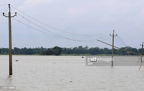 Indian villagers paddle their country boat through flood water at Khalabhuyan village some 60 kms from Guwahati on July 9 2013 More the 100000 people...