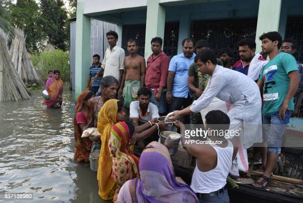 Indian villagers receive relief food near the submerged houses by flood waters in Gazole village at Malda district in the Indian state of West Bengal...