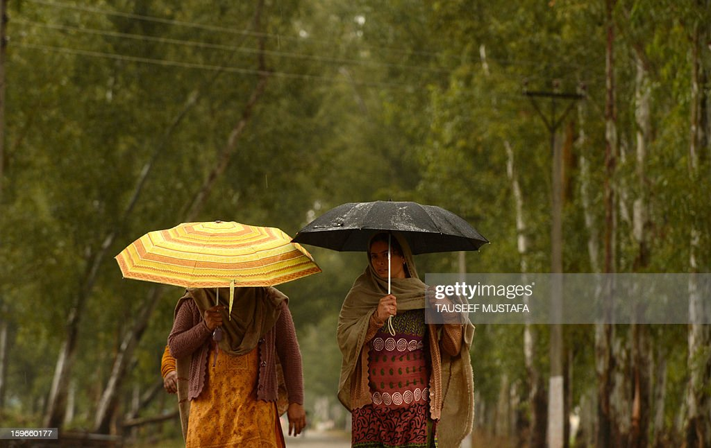 Indian villagers shelter under umbrellas during a rain shower along the India-Pakistan border in Suchit-Garh, 36 kms southwest of Jammu on January 18, 2013. On both sides of the de facto border in Kashmir, villagers living on one of the world's most dangerous flashpoints have special reason to fear the return of tension between India and Pakistan. AFP PHOTO/Tauseef MUSTAFA