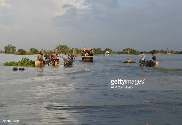 Indian villagers sit along a flooded state highway at Chachol village in Malda district in the Indian state of West Bengal on August 23 2017 More...