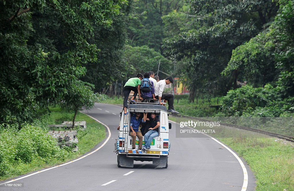 Indian villagers sit atop a vehicle during a day long relaxation of an indefinite strike at Sukna village on the outskirts of Siliguri on August 31, 2013. Gorkha People's Liberation Front (GJM) called an indefinite strike throughout the month in Darjeeling and nearby hills. AFP PHOTO/ Diptendu DUTTA