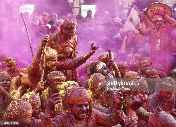 Indian villagers smear themselves with colours during the Lathmar Holi festival at the Nandji Temple on March 7 2017 in Nandgaon near Mathura India...