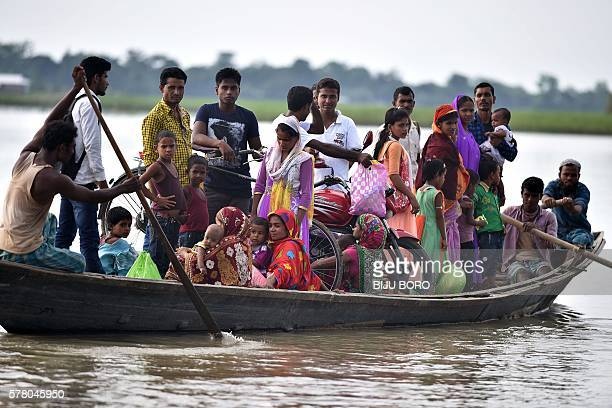 Indian villagers travel by boat over floodwaters in Ashigarh village in the Morigoan district of Assam on July 20 2016 Floods in the northern Indian...