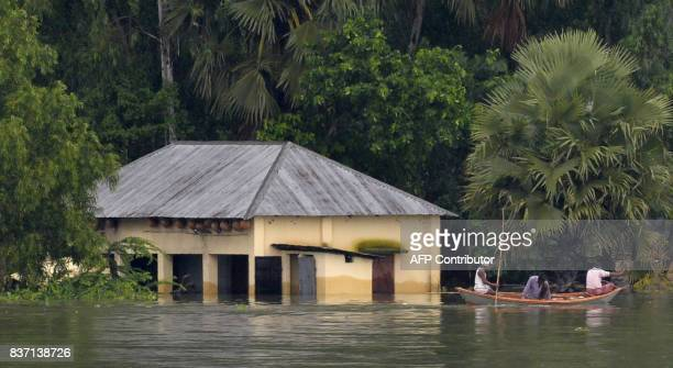 Indian villagers travel on a boat the flooded IndiaBangladesh border area in Jagjiwanpur BOP near Malda district in the Indian state of West Bengal...