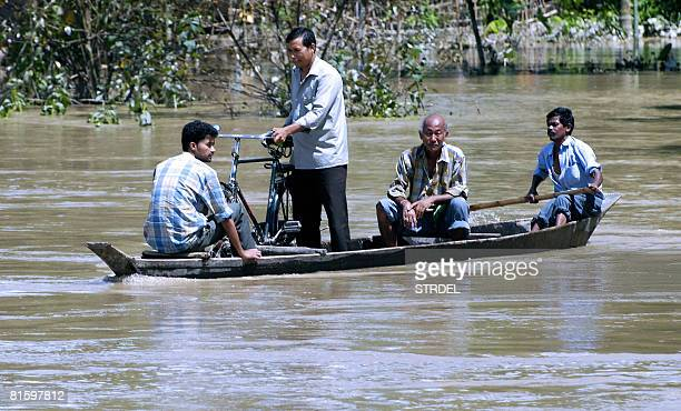Indian villagers travel on a boat through flood water at Kopohua village in the North Lakhimpur district some 400 km from Guwahati on June 17 after...