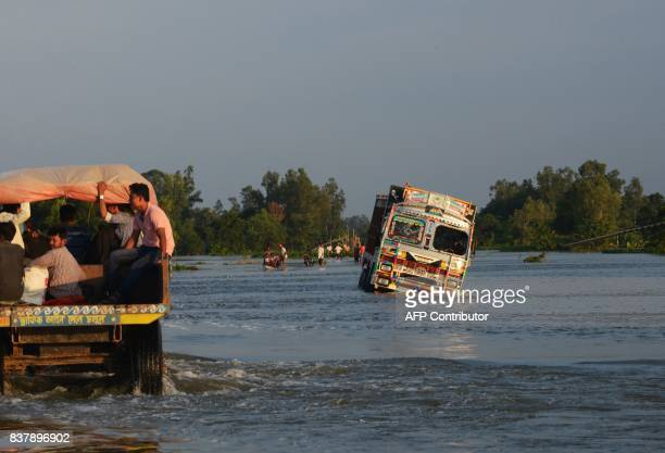 Indian villagers traveling at the back of a truck approach anither truck stuck along a flooded section of a state highway at Chachol village in Malda...