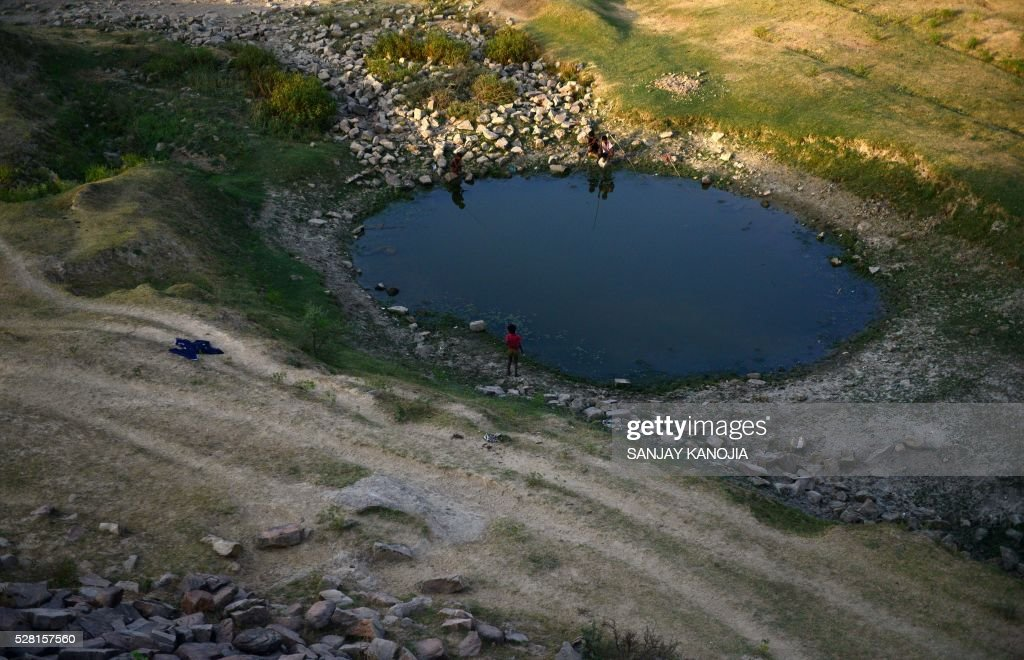Indian villagers try to catch fish in a pool of the shrunken Mansaita River near Allahabad on May 4, 2016. Some 330 million people are suffering from drought in India, the government has said, as the country reels from severe water shortages and desperately poor farmers suffer crop losses. / AFP / SANJAY