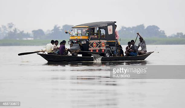 Indian villagers use a boat to transport an autorickshaw through floodwaters in Balimukh village in the Morigaon district of Assam state on August 17...