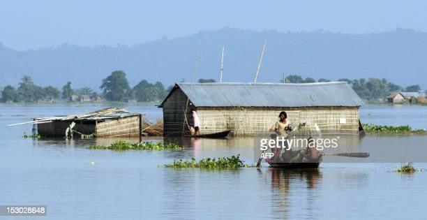 Indian villagers use a boat to travel through floodwaters surrounding the village of Pokoriya some 75kms east of Guwahati on September 29 2012 Rain...