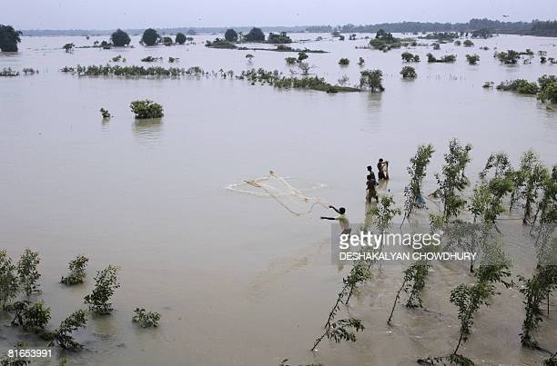 Indian villagers use a fishing net to catch fish in the river 'Keleghai' after it flooded hundreds of villages in both the East and West Midnapore...