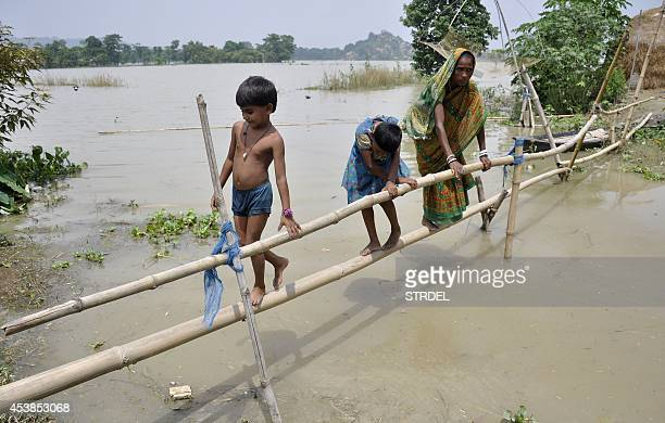 Indian villagers use a makeshift bridge to cross floodwater at Buraburi village in the Morigaon district of the state of Assam on August 20 2014...