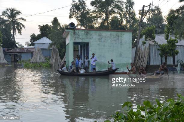 Indian villagers uses boat to collects relief items in Gazole village at Malda district in the Indian state of West Bengal on August 22 2017 More...