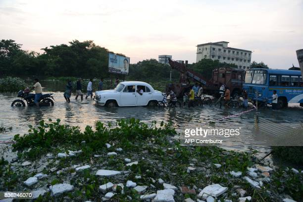 Indian villagers wade next to vehicles a flooded section of national highway 34 at Malda in West Bengal on August 21 2017 More than 750 people have...