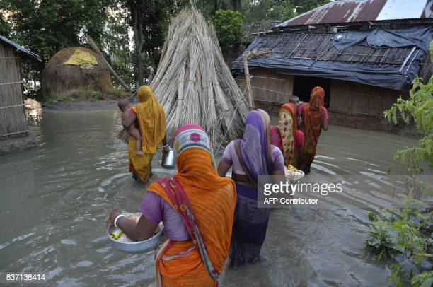 TOPSHOT Indian villagers wade through flood waters after collecting relief food near the submerged houses in Gazole village at Malda district in the...