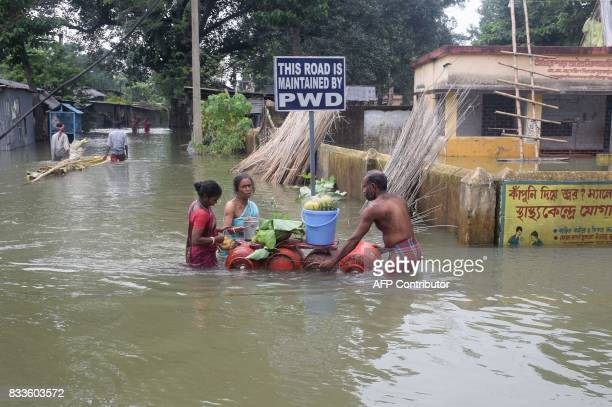 Indian villagers wade through flood waters with a raft made from gas canisters in Balurghat in West Bengal on August 17 2017 At least 221 people have...