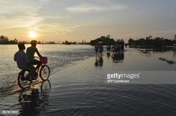 Indian villagers wades through a flooded state highway at Chachol village in Malda district in the Indian state of West Bengal on August 23 2017 More...