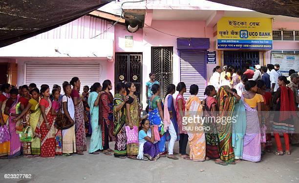 Indian villagers wait in a queue outside a bank to deposit and exchange 500 and 1000 rupee notes in Chandrapur Village some 30 kms from Guwahati on...
